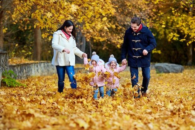 秋の公園で幸せな家族。母親、父親と自然の2人の少女が走って、遊んで、笑っている。