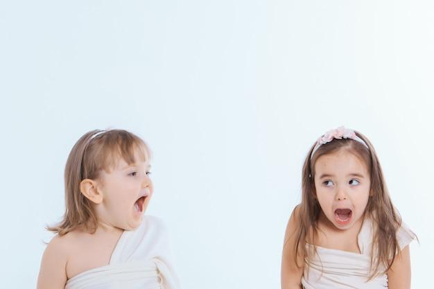 白い背景に口を大きく開いて2人の少女。子供たちは遊んでいます。教育、子供時代、感情、歯科、驚き、友情の概念。コピースペース