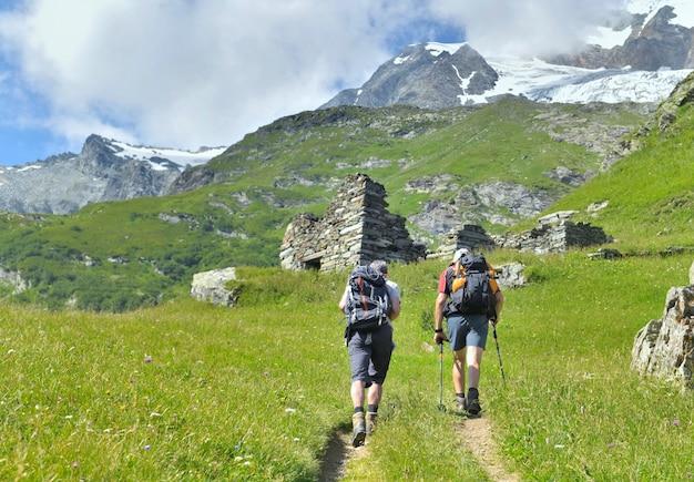 夏の高山氷河への小道を登るバックパックと2人のハイカー