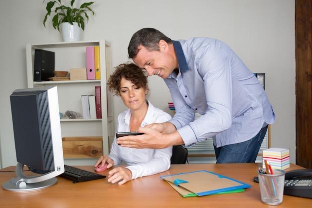 携帯電話を見て仕事で2人のビジネスマン