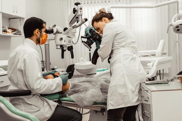 2人の歯科医が患者を治療します。プロのユニフォームと歯科医の機器。ヘルスケア医師の職場を装備します。歯科