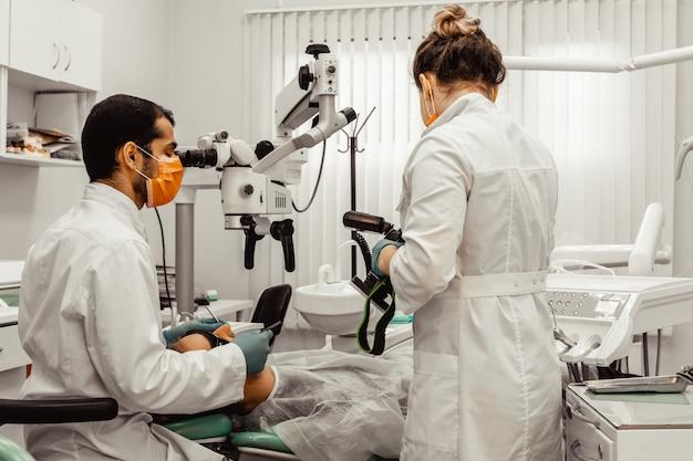 2人の歯科医が患者を治療します。プロの制服と歯科医の機器。ヘルスケア医師の職場を装備。歯科