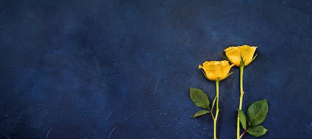 古典的な青色の背景に2つの黄色いバラと長いバナー