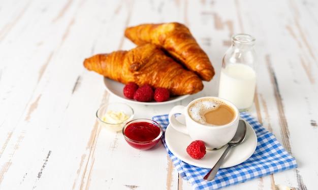 一杯のコーヒーと白いテーブルの上の朝食のための2つのクロワッサン