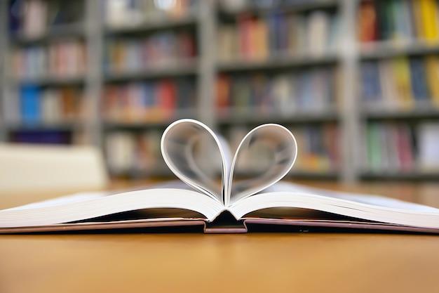 読むライフスタイルのライブラリと2月のバレンタインの日の概念のライブラリでテーブルの上のハート形の本のイメージを閉じます。
