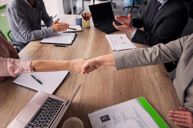 会議室のテーブルの両側に座っている2つの事業チーム。