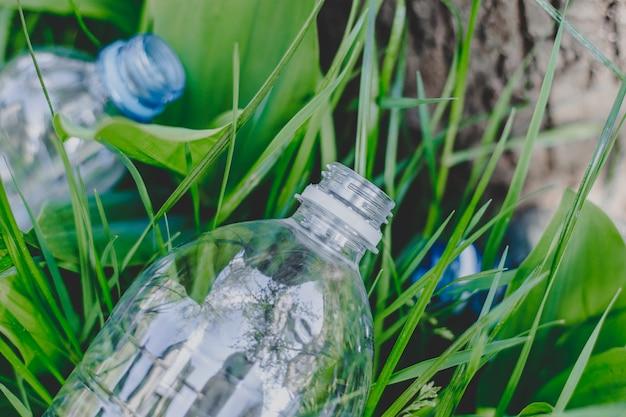 2つのペットボトルが森の地面の芝生に寝転んで