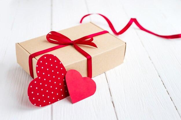 赤いリボン、白い木製の背景の2つの赤いハートのギフトボックス。コピースペースでバレンタインデーの背景