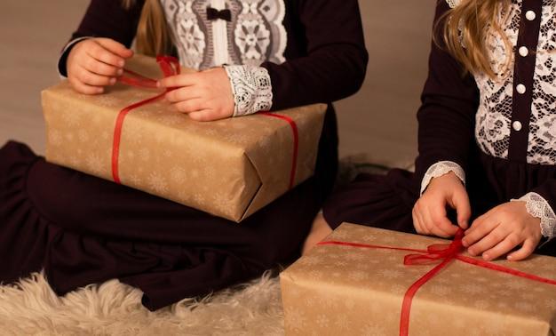 ブルゴーニュレースのレトロなドレスを着た2人の女の子がクリスマスプレゼントを開く
