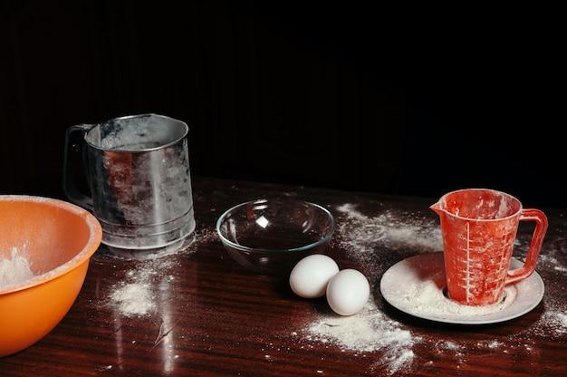 オレンジカップ、計量カップ、スチールふるい、2つの卵は黒いシーンの木製テーブルの上に立つ