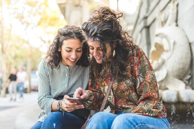 携帯電話を屋外で使う2人の友人の女の子