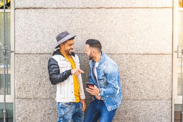 ほほ笑みながら屋外で携帯電話を使用して2つの男性の友人。