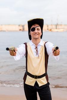 海賊の衣装を着た笑顔の男は、2つのおもちゃの銃をレンズに向けた。
