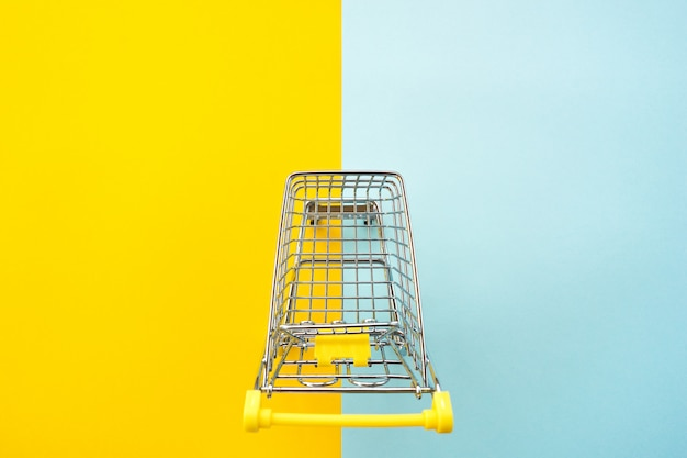 2色の黄色青色の背景の製品のおもちゃのカート。
