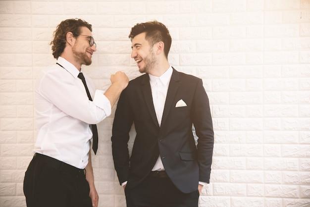 屋内で余暇の間に一緒に話している2つの若いスマートビジネスマン