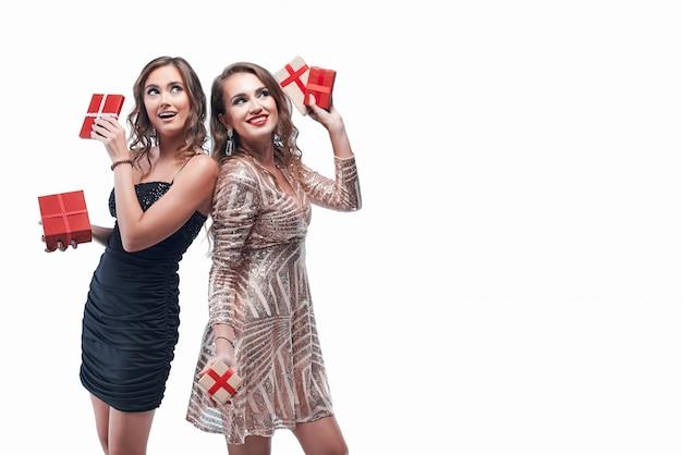 白で隔離の手の中に赤いプレゼントを持つ2人の若い女の子