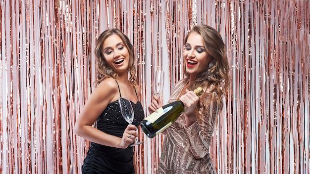 輝く装飾に対してシャンパンを飲む2人の美しいエレガントな女性