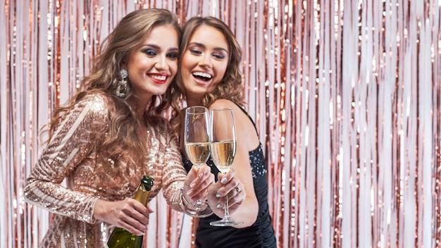 シャンパングラスをチリンと2人の美しいエレガントな女性。