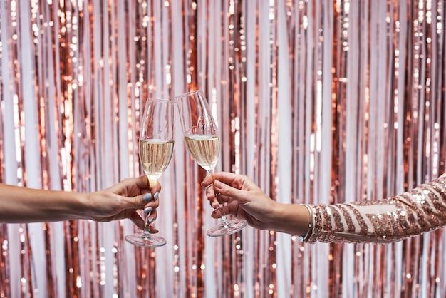 シャンパングラスをチリンと2つの女性の手のクローズアップ。