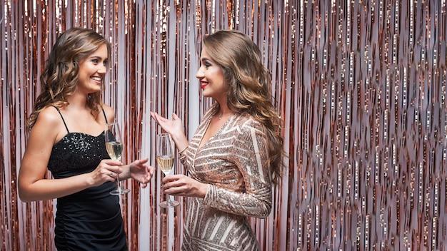 シャンパンを話したり飲んだりするイブニングドレスを着た2人のエレガントな女性の友人。