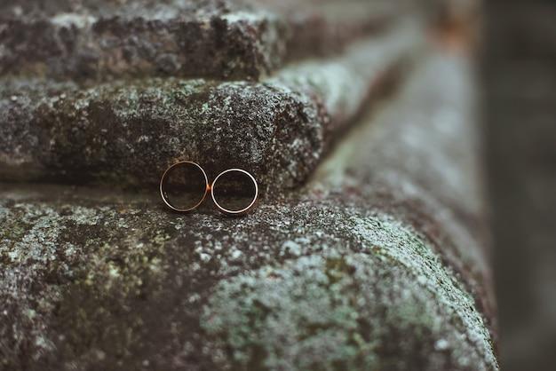 石の上に横たわる2つの結婚指輪のクローズアップ