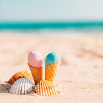 ビーチで貝殻を持つ2つのおいしいアイスクリーム