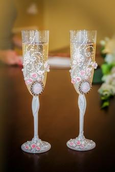 シャンパンの2つの結婚式のメガネはテーブルの上に立つ
