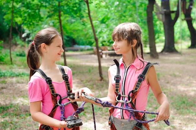 アドベンチャークライミングハイワイヤーパーク-ロープパークでハイキング2人の女の子