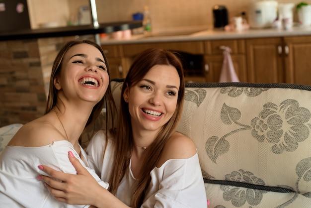 自宅のソファーに座っているブルージーンズの2つの若い美しい陽気なガールフレンドは笑っています。