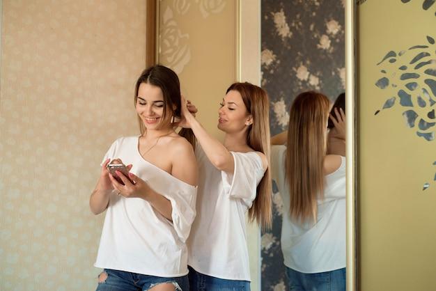 2人の美しい笑顔の姉妹またはガールフレンドがパーティーに行き、家でお互いの髪型を作ります。
