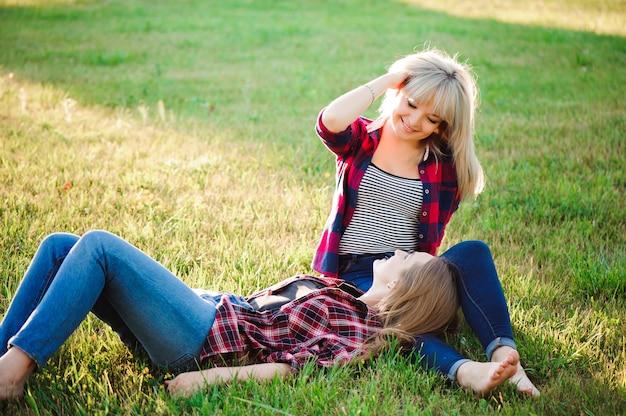 2 счастливых подруги играя и имея удовольствие в зеленой траве