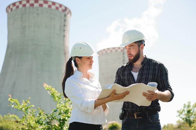 発電所に立っている2人のエンジニアが計画について話し合っています。