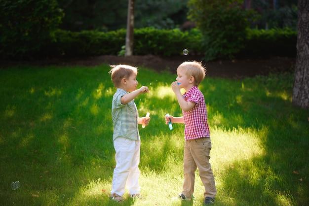 屋外の泡で遊ぶ2人の幸せな少年