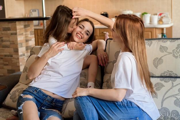 2 сестры и маленькая дочь усмехаясь и обнимая дома внутреннюю предпосылку.