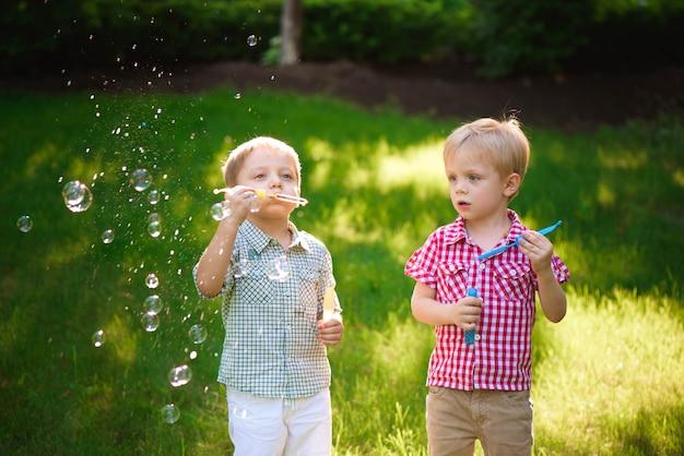 屋外の泡で遊ぶ2つの幸せな少年