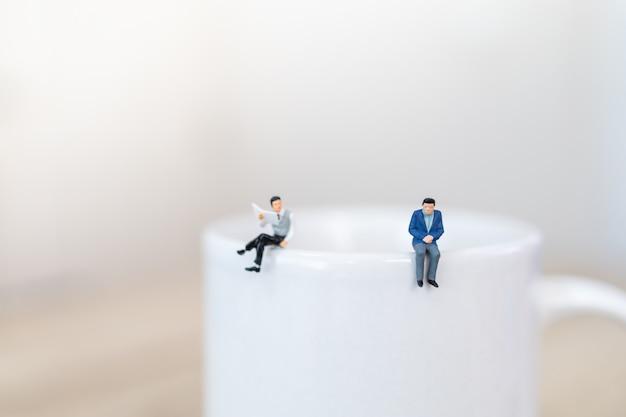 社会的な距離を持つホットコーヒーの白いマグカップの上に立っている2人のビジネスマンのミニチュアフィギュアの人々。