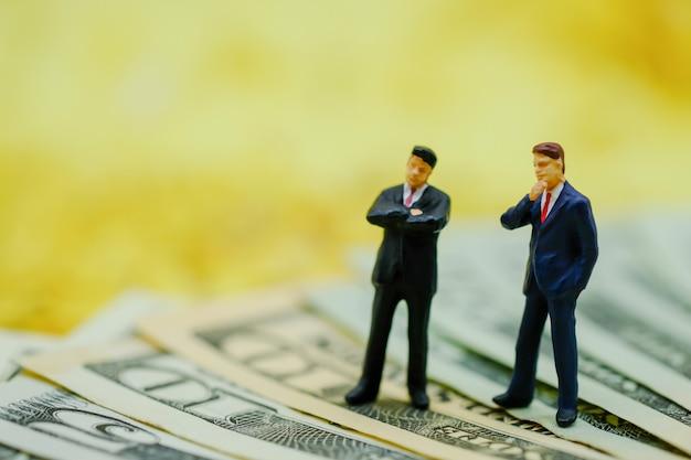 ビジネスとお金の概念。米ドル紙幣の上に立って2つの実業家ミニチュアフィギュア。