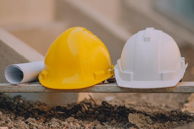 建設現場での木に2つのヘルメットハード帽子の青写真