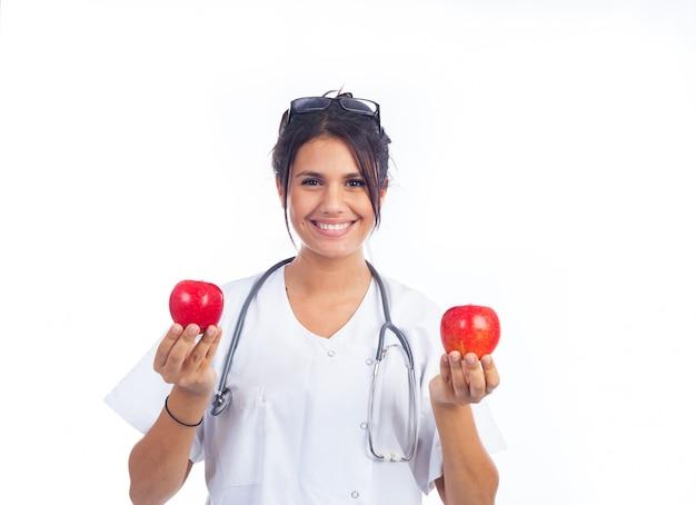 Молодой женский доктор показывая 2 красивых красных яблока