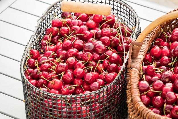 庭のテーブルに美しい赤いサクランボでいっぱいの2つのバスケット