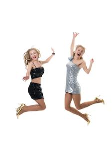 2人の美しい幸せな女の子が分離された白でジャンプしています。買い物の喜びフリーズジャンプ、女の子の飛行。