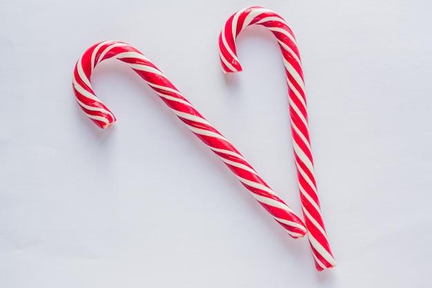白い背景の上の2つのキャンディー杖。伝統的なクリスマスのお菓子。