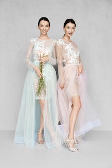 壁の近くでポーズをとってレース詳細と淡い透明のドレスを着ている2人の美しい女性