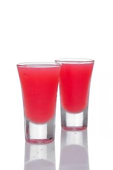 白で隔離される反射とショットグラスに2つのイチゴのカクテル