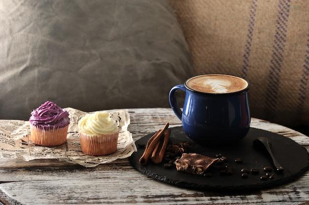 ミルクフォームとカップケーキ2個付きマグカップのカフェカプチーノでの朝の朝食