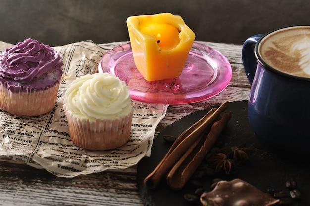 ミルクの泡とカップケーキ2個とキャンドルが入ったマグカップのカプチーノ