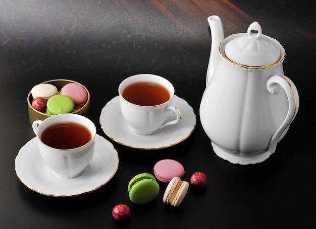 モーニングティー-紅茶とマカロンを入れた2つのマグカップ