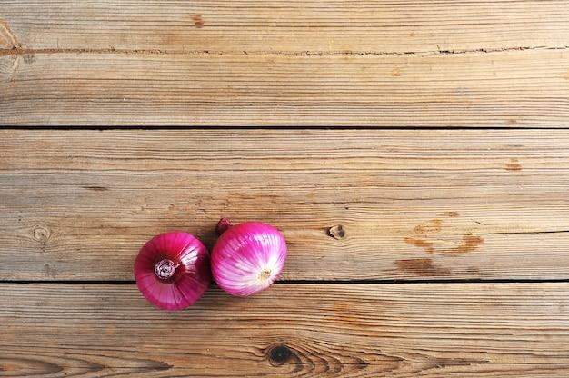 素朴な木製の背景に2つの赤玉ねぎ