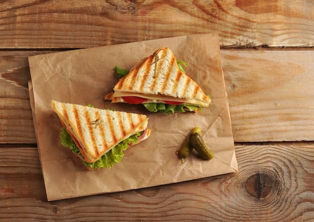 木製の表面にペーパータオルに2つのサンドイッチピクルス