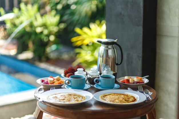 木製のテーブルにホットドリンクの2つの青いカップと伝統的なバリの朝食